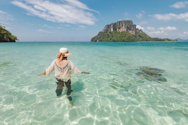 Mulher asiática em pé e brincando no mar e curtindo com a beleza natural em suas férias. conceito de férias de verão.