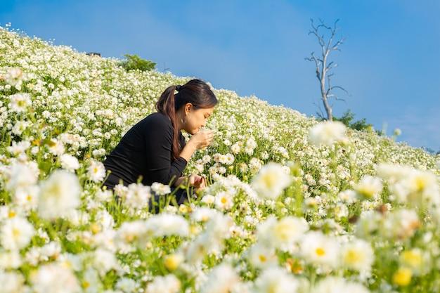 Mulher asiática em pé e jogando uma flor atmosfera comovente no campo de crisântemo