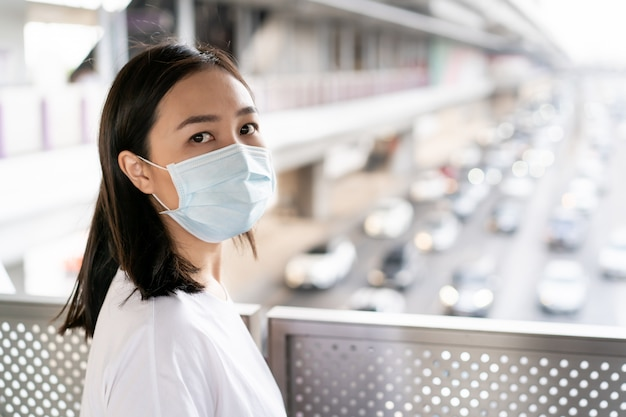 Mulher asiática em pé na ponte na cidade totalmente com poeira pm2.5. mulher usando máscara protetora para se proteger do vírus covid19. preocupação da mulher com a doença da covid-19. crise de coronavírus.