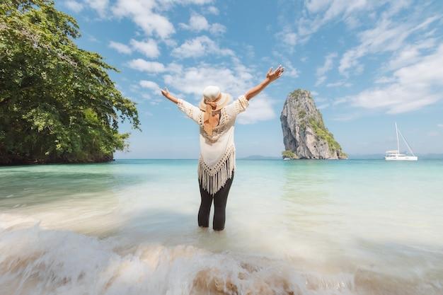 Mulher asiática em pé no mar e curtindo com lindo mar e céu em suas férias. conceito de férias de verão.