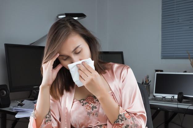 Mulher asiática em pijamas de cetim sentindo mal e espirrar na mesa em casa