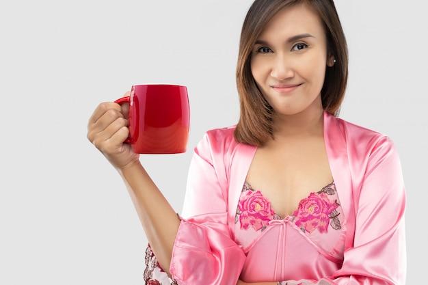 Mulher asiática em roupa de noite e roupão de seda rosa, bebendo leite em um copo vermelho antes de ir para a cama