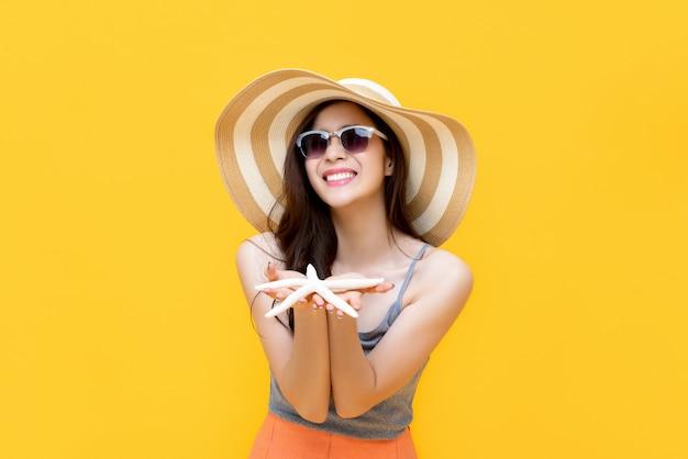 Mulher asiática em roupas casuais de verão sorrindo e segurando estrela do mar nas mãos