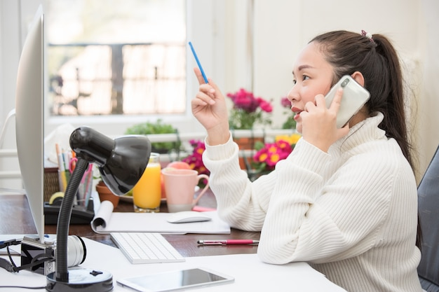Mulher asiática em roupas casuais está trabalhando com telefone e laptop para se comunicar na internet com os clientes na sala