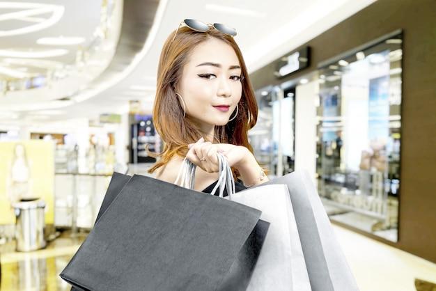 Mulher asiática em roupas pretas e óculos de sol carregando sacolas de compras no shopping