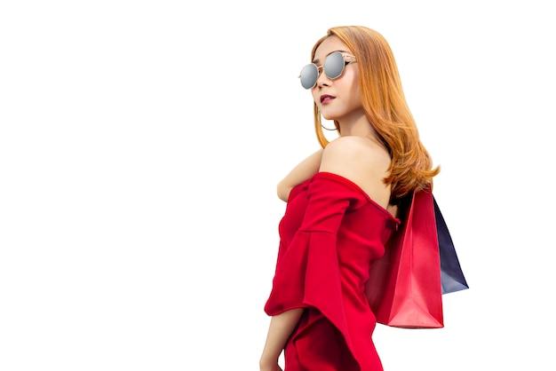 Mulher asiática em roupas vermelhas e óculos de sol carregando sacolas de compras