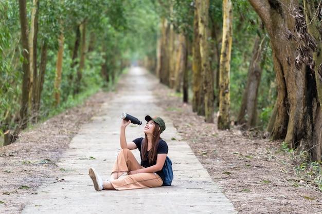 Mulher asiática em traje casual, beber a água da garrafa de esporte com ação de relaxamento em profundidade