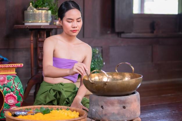 Mulher asiática em traje de empregada doméstica antiga no período de ayutthaya. ela está sentada fazendo sobremesas tailandesas tradicionais