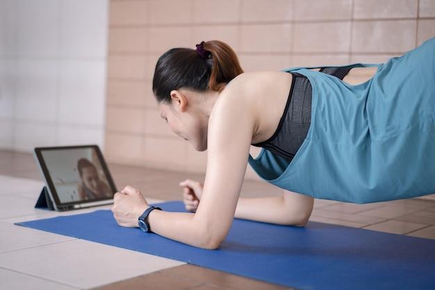 Mulher asiática em trajes esportivos treina após um programa de treinamento online via tablet digital em casa