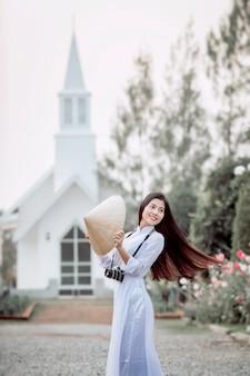 Mulher asiática em trajes tradicionais do vietnã, em pé, posando enquanto tirava uma foto da igreja cristã