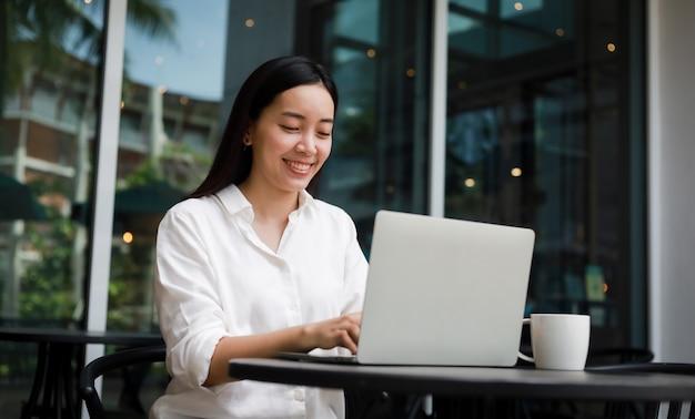 Mulher asiática em um café trabalhando em um laptop