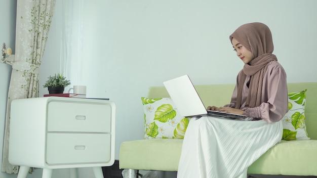 Mulher asiática em um hijab sentada desfrutando de algo em seu laptop