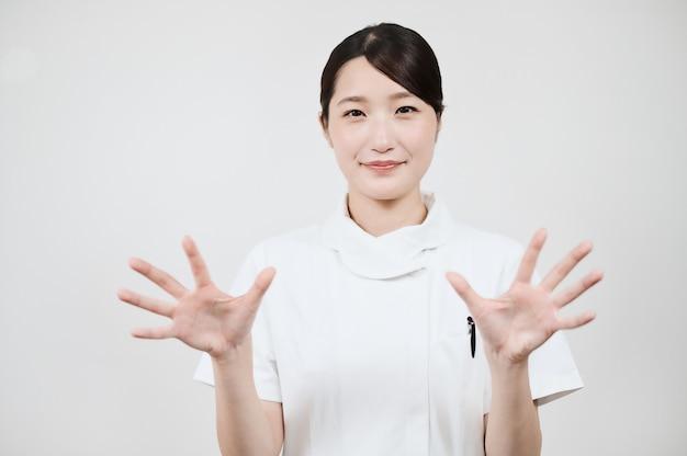Mulher asiática em um jaleco branco posando com as mãos abertas