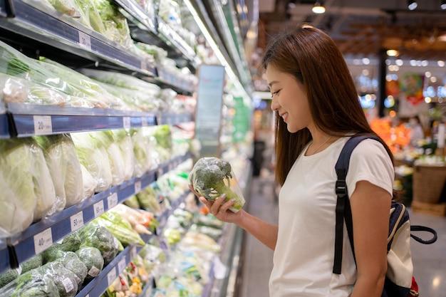 Mulher asiática em um supermercado escolhendo vegetais verdes nas prateleiras
