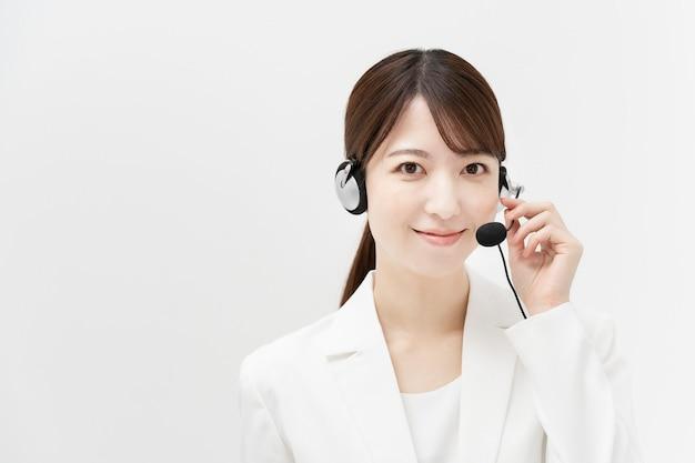 Mulher asiática em um terno branco usando um fone de ouvido com um sorriso