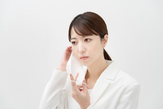 Mulher asiática em um terno branco usando uma máscara e fundo branco
