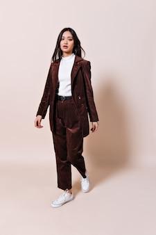 Mulher asiática em um terno de veludo cotelê olhando para a frente na parede bege