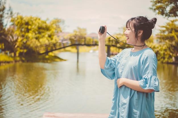 Mulher asiática em um vestido azul em um parque público carregando uma câmera digital mirrorless e tirando uma foto