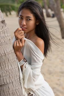 Mulher asiática em um vestido branco, caminhando na praia tropical.