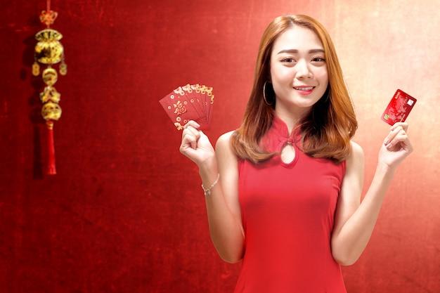 Mulher asiática em um vestido cheongsam segurando um cartão de crédito e envelopes vermelhos