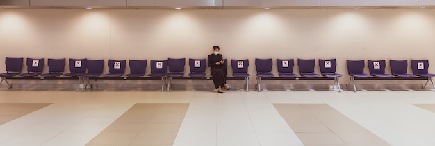 Mulher asiática em um vestido preto, usando uma máscara protetora de higiene, sentada sozinha em cadeiras de fileira e usando um smartphone.
