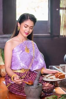 Mulher asiática em um vestido tradicional roxo e joias cozinhando na cozinha da casa de madeira.