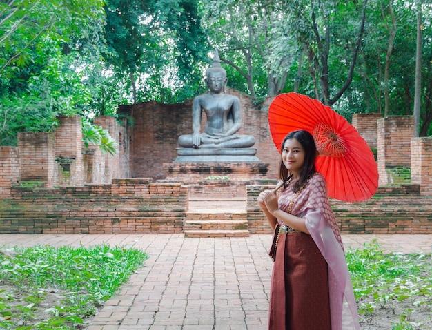 Mulher asiática em um vestido tradicional tailandês com guarda-chuva vermelho em frente à antiga estátua de buda