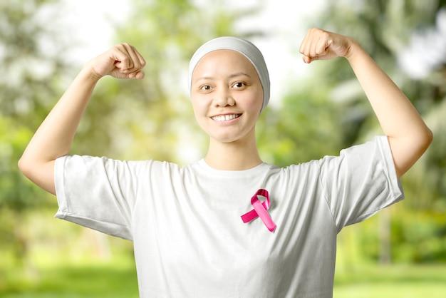 Mulher asiática em uma camisa branca com uma fita rosa com um parque verde