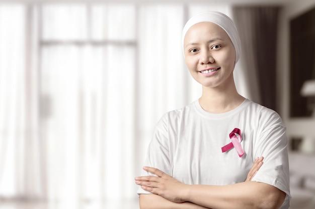 Mulher asiática em uma camisa branca com uma fita rosa em casa