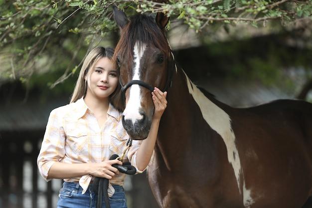 Mulher asiática em uma fantasia de cowgirl fica com um cavalo em uma fazenda de gado.