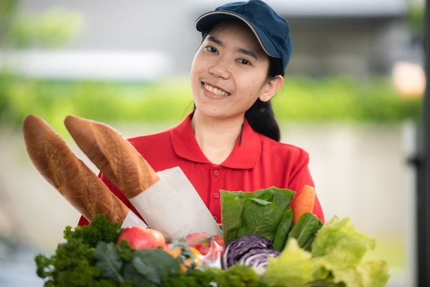 Mulher asiática em uma sacola de manuseio de uniforme vermelho com comida, frutas e vegetais entregues ao cliente na frente da casa, conceito de serviço de entrega
