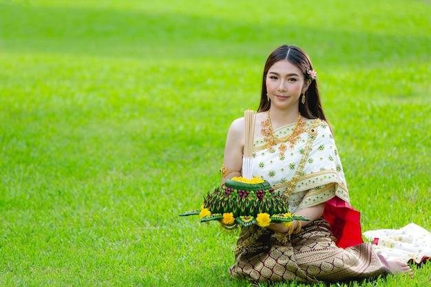 Mulher asiática em vestido tailandês tradicional realiza festival kratong loy krathong