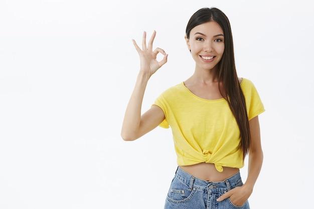 Mulher asiática encantadora confiante e assertiva com longos cabelos escuros e sem maquiagem se sentindo bonita