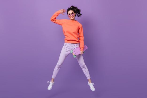 Mulher asiática engraçada em calças pulando sobre fundo roxo. visão de comprimento total de uma jovem coreana com longboard.
