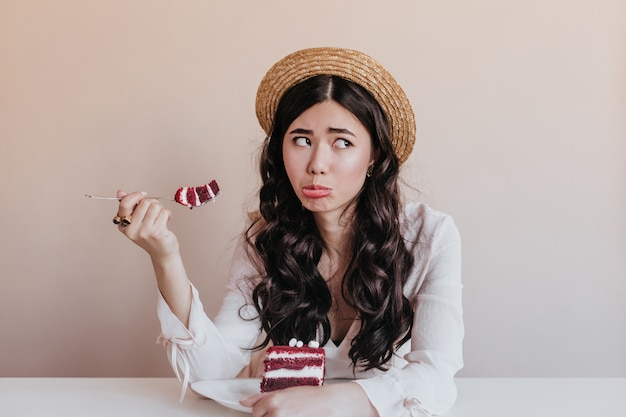 Mulher asiática engraçada no chapéu de palha comendo bolo. modelo feminino chinês bonito apreciando a sobremesa.