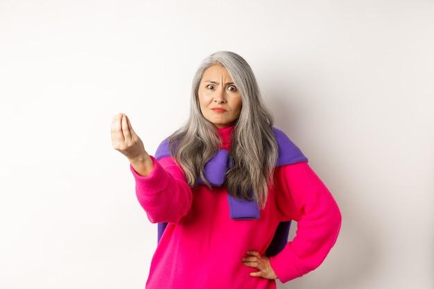 Mulher asiática engraçada olhando com raiva e confusa, apertando os dedos, em pé mal-humorado contra um fundo branco. copie o espaço