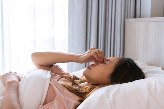 Mulher asiática enjoada deitada na cama
