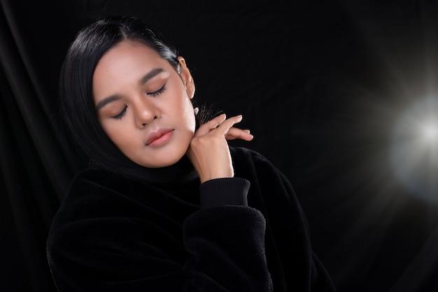 Mulher asiática enrola o cabelo preto longo e liso em volta do rosto e pescoço em estilo fashion, sobre um lindo fundo de cortina preta vazando luz cópia espaço