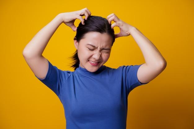 Mulher asiática entediada e irritada, coçando a cabeça, no amarelo.