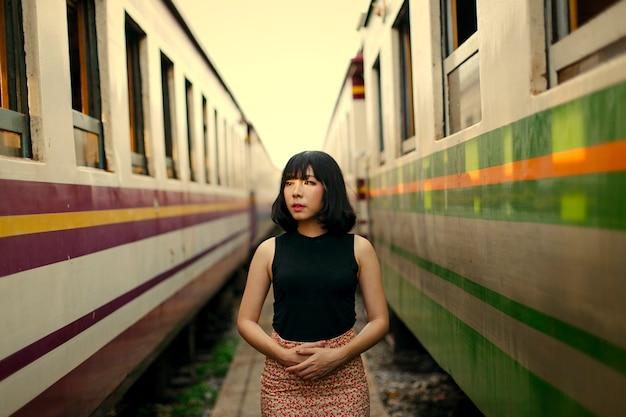 Mulher asiática entre dois trens
