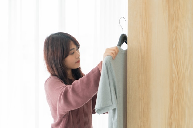 Mulher asiática escolhendo roupas em um quarto
