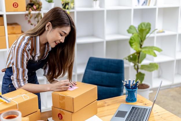 Mulher asiática escrevendo informações de remessa de clientes em uma caixa de pacote, ela é proprietária de uma loja online e envia produtos para clientes por meio de uma empresa de courier privada. conceito de venda online.