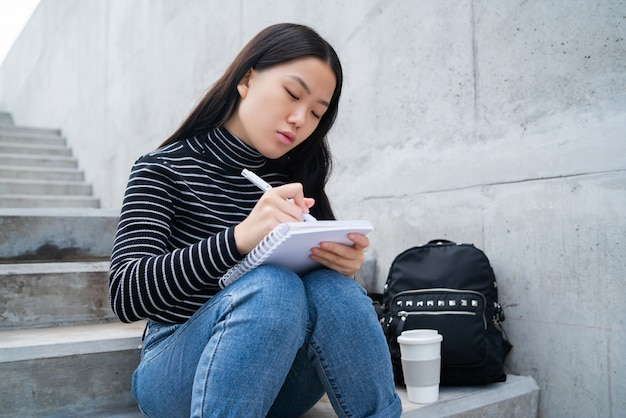Mulher asiática, escrevendo no caderno.