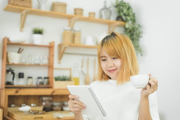 Mulher asiática escrever listas de compras no bloco de notas por caneta no balcão da cozinha em casa e ler