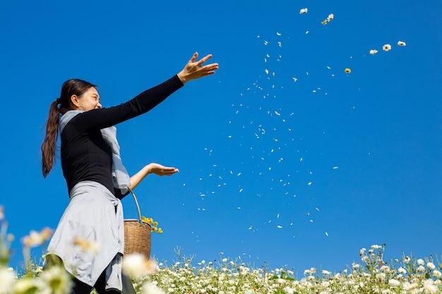 Mulher asiática espalhar flor de crisântemo para o céu azul no jardim florido.