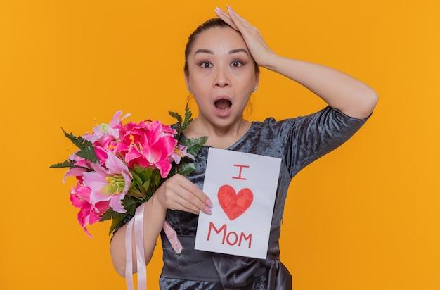 Mulher asiática espantada e surpresa segurando um cartão e um buquê de flores comemorando o dia das mães em pé sobre uma parede laranja