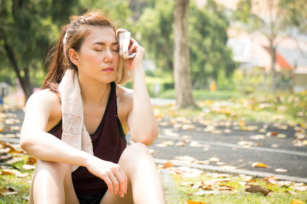 Mulher asiática esporte é julgada e descansar depois de correr no parque