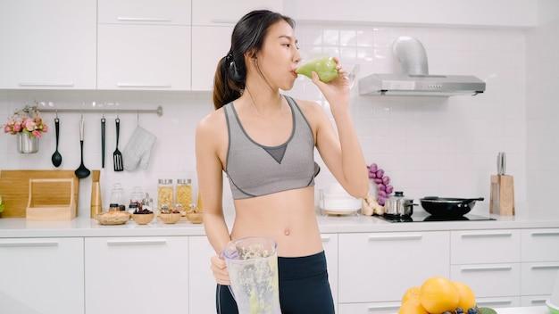 Mulher asiática esportiva bebendo suco de maçã na cozinha