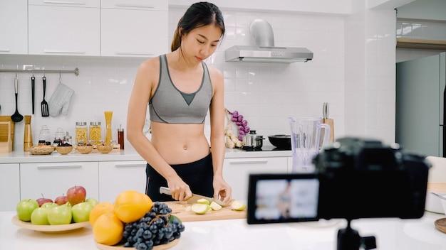 Mulher asiática esportiva do blogger usando uma câmera gravando como fazer um vídeo de suco de maçã para seu assinante