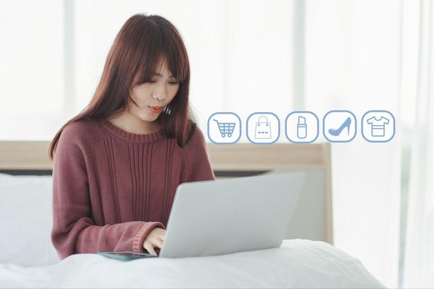 Mulher asiática está gostando de fazer compras online em seu laptop na cama. conceito de compras online.